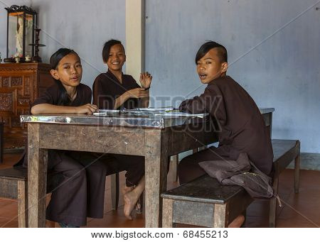 Three Young Boys Monks Studying In Classroom At Royal Buddhist Thien Mu Pagoda.