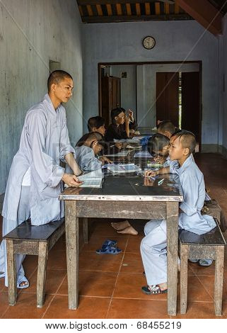 Teacher And Young Boys Monks Studying In Classroom At Royal Buddhist Thien Mu Pagoda.