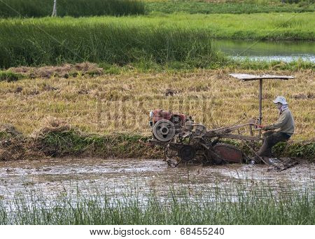 Farmer Plows Through Muddy Rice Paddy With Motorized Machine.