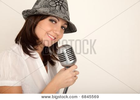 Portrait of girl wearing hat in white shirt with microphone on rack against white wall. Horizontal f