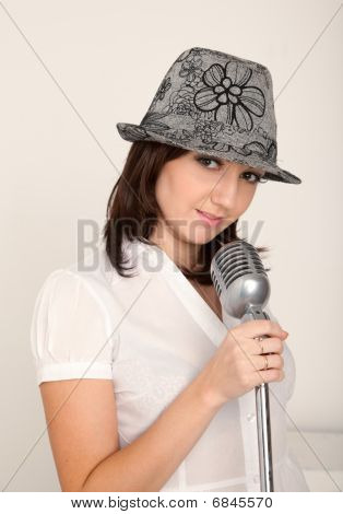 Portrait of girl wearing hat in white shirt with microphone on rack against white wall.