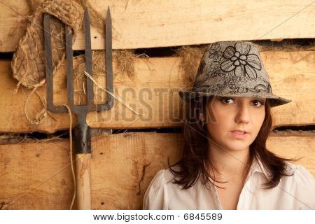 Portrait of girl in hat in hayloft with pitchfork and bast shoes. Horizontal format.