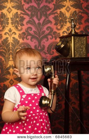 Little girl in red dress talking vintage phone. Interior in retro style. Vertical format.
