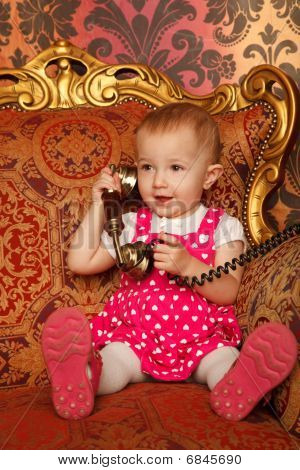 Little girl in red dress talking vintage phone. Interior in retro style. Close up. Vertical format.