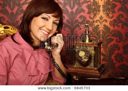 Portrait of girl in red shirt sitting in armchair talking retro phone.