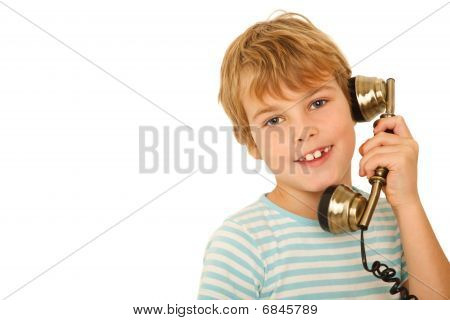 Portrait of boy in T-shirt talking to retro phone against white background