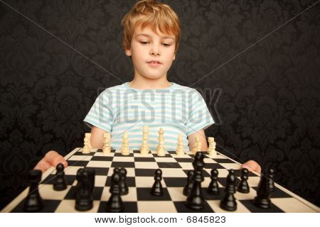 Portrait of boy in T-shirt with chessboard against the wall with ornament