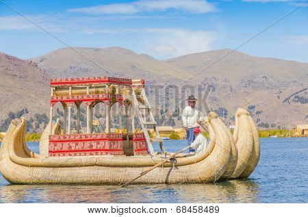PUNO, PERU, MAY 5, 2014 - Local men in traditional attires row sitting in reed boat (