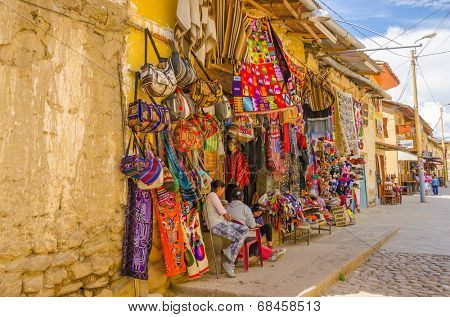 PERU, OLLANTAYTAMBO, MAY 4, 2014 - . Souvenirs' sellers sit in front of their boutique in Plaza de Armas
