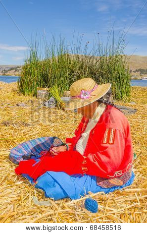 PUNO, PERU, MAY 5, 2014 - Women in traditional attire does some embroidery on floating Uros islands on Lake Titicaca