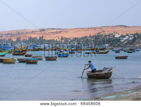 Man Rows Supplies To The Fishing Fleet Anchored Off Coast.