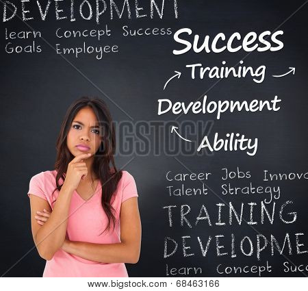 Pretty brunette thinking against blackboard with business buzzwords