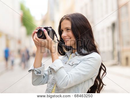tourism, travel, leisure, holidays and friendship concept - smiling teenage girl with camera taking picture on street
