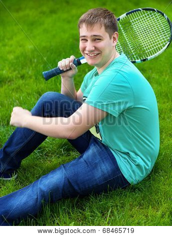 Teenage Boy Smiling While Holding A Tennis Racket