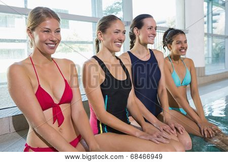 Female aqua aerobics class smiling in swimming pool at the leisure centre