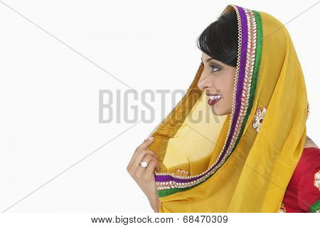 Side view of Indian female holding dupatta over gray background