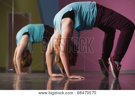 Pretty break dancer doing a back bend in the dance studio