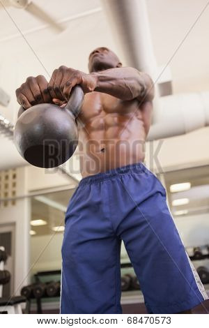Low angle view of shirtless young muscular man lifting kettle bell in gym