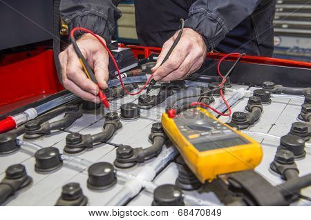 Man, checking the nodes of the battery pack of a forklift, using a multimeter