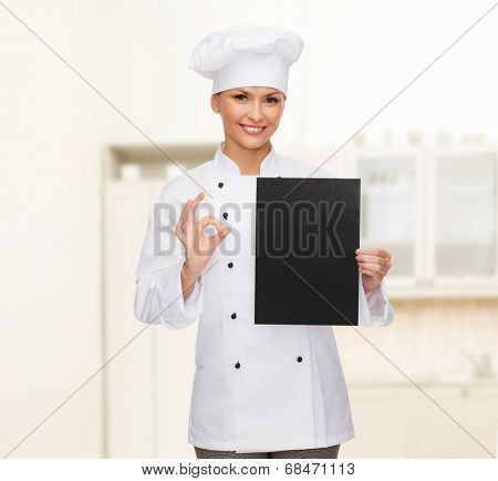 cooking, advertisement and food concept - smiling female chef, cook or baker with blank black paper showing ok sing