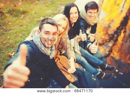 holidays, vacation, happy people concept - group of friends or couples having fun and showing thumbs up in autumn park