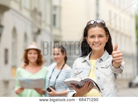 tourism, travel, leisure, holidays and friendship concept - smiling teenage girls with city guide, map and camera showing thumbs up outdoors