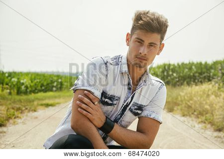 Handsome Young Man Sitting In Coutryside Dirt Road