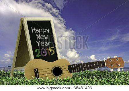 Ukulele with blue sky and Blackboard 2015 text on the grass