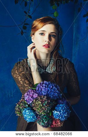 portrait of a beautiful woman with red hair in curly braided hairstyle. wearing a romantic lace dress and holding flowers on grunge painted background