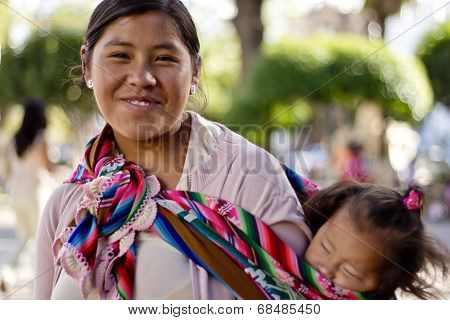 Sucre, Bolivia - January 17, 2012: A Bolivian Mom Carries Her Child On Her Back, Tied Up With A Colo