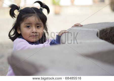 Sucre, Bolivia - January 17, 2012: A Little Girl Plays Around The Historical Buildings Of The Consti