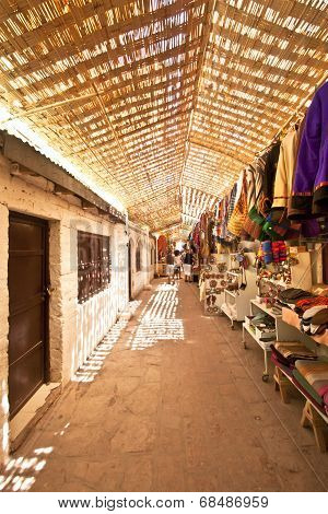 A Street Market In The Middle Of The Desert With A Straw Roof As Coverage.