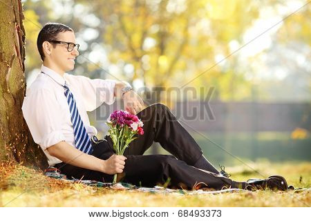 Young man with bunch of flowers sitting on a grass and checking the time, in a park