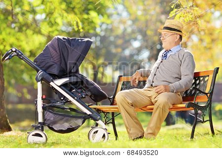 Grandfather sitting and looking at his baby nephew in a stroller, in a park