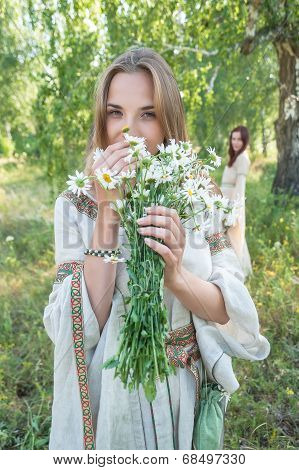Beautiful blonde woman with bouquet of camomiles