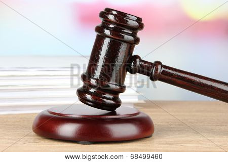 Gavel and documents on table on light background