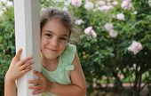 image of gazebo  - Beautiful little girl smiling and hugging a gazebo pole - JPG
