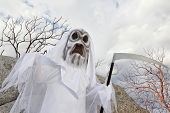 stock photo of grim-reaper  - Boy dressed up as grim reaper holding scythe - JPG