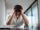 stock photo of frustrated  - frustrated with problems young business man working on laptop computer at home - JPG