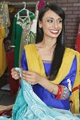 image of dupatta  - Indian female dressmaker looking away while holding sari - JPG