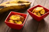 stock photo of plantain  - Fried slices of the ripe plantain in small red bowls which can be eaten as snack or is used to accompany dishes in some South American countries ripe plantains in the back  - JPG