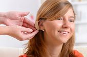 image of deaf  - Putting on a deaf aid - JPG