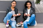 stock photo of  friends forever  - Two north African teen friends drinking together coffee outside - JPG