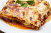 picture of lasagna  - hot freshly made home lasagna close up in plate with parsley leaf - JPG