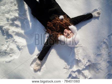 Happy teenage girl lying in the deep snow on beautiful winter day.