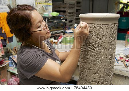 Woman cuts traditional tattoo motives decoration at kaolin, Kuching, Malaysia.