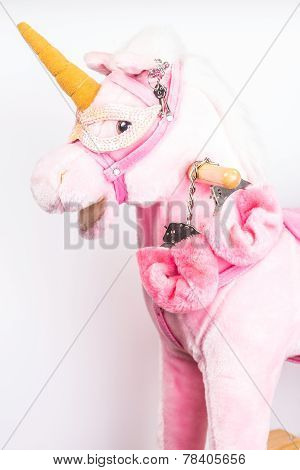 concept love. handcuffs on a toy pink unicorn