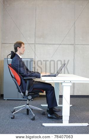 white man in suit in correct sitting position at workstation in office