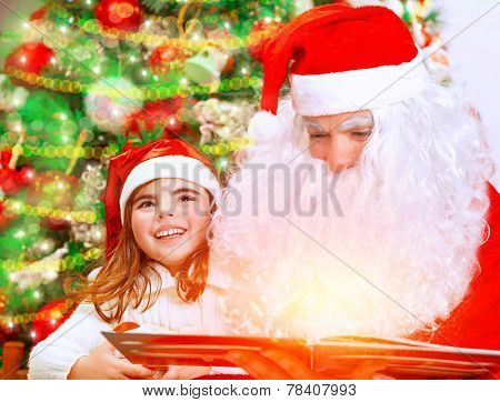 Santa Claus with little granddaughter opening magic book and saw glowing lights, spending Christmas eve near beautiful decorated tree