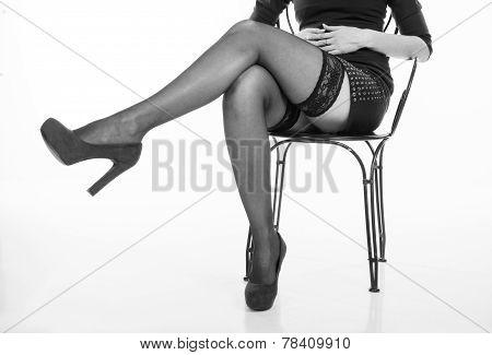 Long Slender Female Legs Of Girl Sitting On A Chair In Black Stockings